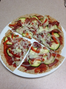 A low-carb tortilla topped with tomato paste, veggies and ham make an excellent low-carb dinner.